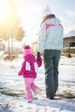 Mutter und Tochter, die zusammen an einem Tag des verschneiten Winters gehen stockbild