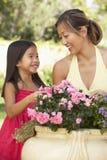 Mutter und Tochter, die zusammen im Garten arbeiten lizenzfreies stockbild