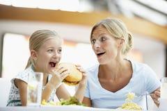 Mutter und Tochter, die zusammen am Kaffee zu Mittag essen Stockbilder