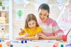 Mutter und Tochter, die zusammen malen Stockbild