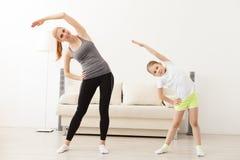 Mutter und Tochter, die zusammen Yoga tun lizenzfreies stockfoto