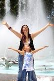 Mutter und Tochter durch Brunnen Stockbilder