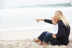 Mutter und Tochter am Feiertag, der auf Strand sitzt Lizenzfreie Stockfotos