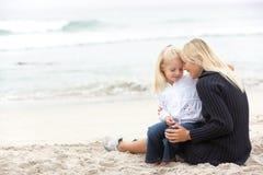 Mutter und Tochter am Feiertag, der auf Strand sitzt Stockbild
