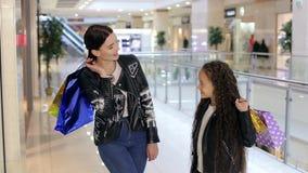 Mutter und Tochter gehen in das Mall mit Taschen in ihren Händen stock footage