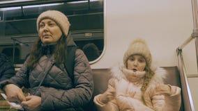 Mutter und Tochter gehen in das U-Bahnauto Müdes jugendlich Mädchen tanzt und schläft ein stock footage