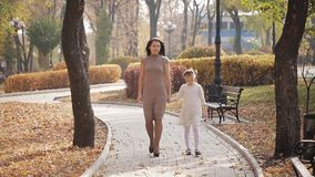 Mutter und Tochter gehen entlang eine Allee, die mit gelbem Laub des Herbstes gestreut wird Glückliche Familie auf einem Weg im S stock footage