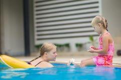 Mutter und Tochter haben Spaß an der Poolseite in tropischem Strand reso Stockfotografie