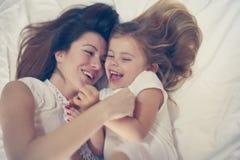 Mutter und Tochter im Bett zusammen Stockbild