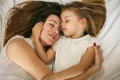 Mutter und Tochter im Bett zusammen Stockbilder
