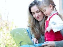 Mutter und Tochter im Freien mit Notizbuch Stockfoto
