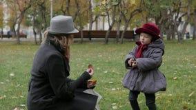 Mutter und Tochter im Park, der werfende Blätter spielt stockfotografie