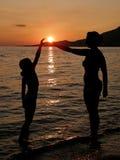 Mutter und Tochter im Sonnenuntergang auf Strand Stockfotos