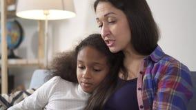 Mutter und Tochter konzentriert auf das Ablesen des pädagogischen Buches im Wohnzimmer stock video