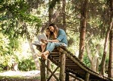 Mutter und Tochter lasen ein Buch im Park lizenzfreie stockfotografie