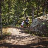 Mutter und Tochter lassen laufen und haben Spaß auf einem Wanderweg lizenzfreie stockfotografie