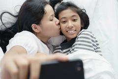 Mutter und Tochter machen ein Foto zusammen Asiatinnen und nettes Mädchenso Spaß- und glückliches selfie auf dem Bett stockbilder