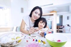 Mutter und Tochter malen Ostereier im Haus Lizenzfreies Stockfoto