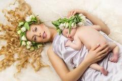 Mutter und Tochter mit Blumendekor auf Kopf Lizenzfreie Stockfotos