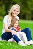 Mutter und Tochter mit dem Apfel, der auf dem grünen Gras sitzt Stockfotografie