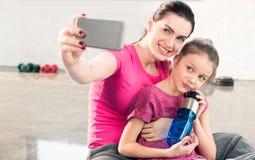 Mutter und Tochter mit der Flasche, die zusammen sitzt und selfie in der Turnhalle nimmt Lizenzfreies Stockbild