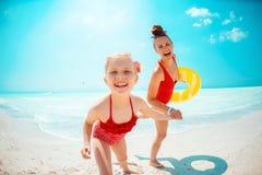 Mutter und Tochter mit gelbem aufblasbarem Rettungsring auf Strand lizenzfreies stockfoto