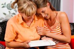 Mutter und Tochter mit Geschenk stockfotografie