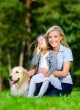 Mutter und Tochter mit golden retriever sind auf dem Gras Stockfoto