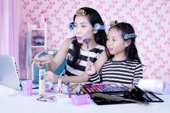 Mutter und Tochter mit Haarlockenwickler aufpassend, wie man Tutorium herrichtet lizenzfreie stockfotografie