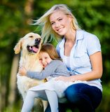 Mutter und Tochter mit Haustier sind auf dem Gras Lizenzfreie Stockbilder