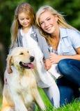 Mutter und Tochter mit Hund sind auf dem grünen Gras Lizenzfreie Stockbilder