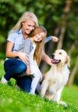Mutter und Tochter mit labrador retriever sind auf dem Gras Stockfotos