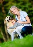 Mutter und Tochter mit Retriever im Park Stockbilder