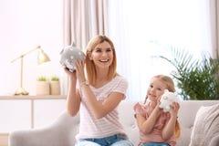 Mutter und Tochter mit Sparschweinen stockbilder