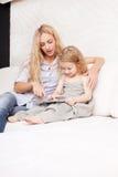 Mutter und Tochter mit Tablette am Sofa Stockbild