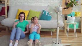 Mutter und Tochter nahe bei dem Fan leidet unter heißem Wetter stock video