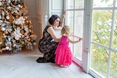 Mutter und Tochter nahe einem Weihnachtsbaum Lizenzfreie Stockfotos