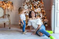 Mutter und Tochter nahe einem Weihnachtsbaum Stockbilder