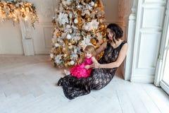 Mutter und Tochter nahe einem Weihnachtsbaum Stockfotos