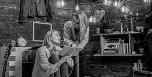 Mutter und Tochter oder Schwestern, die zusammen, Literaturkonzept lesen Frau verwirrt durch Plantorsion im Roman Mädchen aufgere stockbild