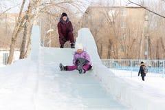 Mutter und Tochter reiten von einem schneebedeckten Berg Stockbilder
