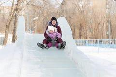 Mutter und Tochter reiten von einem schneebedeckten Berg Lizenzfreies Stockfoto