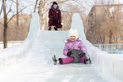 Mutter und Tochter reiten von einem schneebedeckten Berg Lizenzfreie Stockfotos