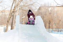 Mutter und Tochter reiten von einem schneebedeckten Berg Lizenzfreie Stockfotografie