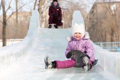 Mutter und Tochter reiten von einem schneebedeckten Berg Lizenzfreies Stockbild
