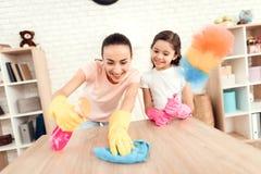 Mutter und Tochter säubern zu Hause Wischen Sie die Regale und die Tabelle ab stockfotografie