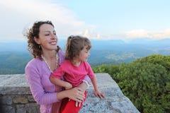 Mutter und Tochter schauen auf Berg vom Balkon lizenzfreie stockfotografie