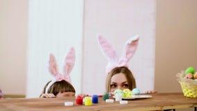 Mutter und Tochter schauen heraus von hinten die Tabelle, die ein Korb von Ostereiern und Farbe ist stock video footage