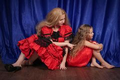 Mutter und Tochter sind beleidigt sitzend und auf dem Boden Mutter versucht, Frieden und Freundschaft mit dem Kind herzustellen lizenzfreie stockfotografie