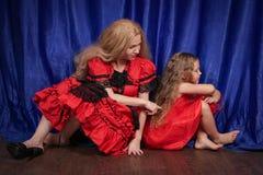 Mutter und Tochter sind beleidigt sitzend und auf dem Boden Mutter versucht, Frieden und Freundschaft mit dem Kind herzustellen lizenzfreie stockbilder